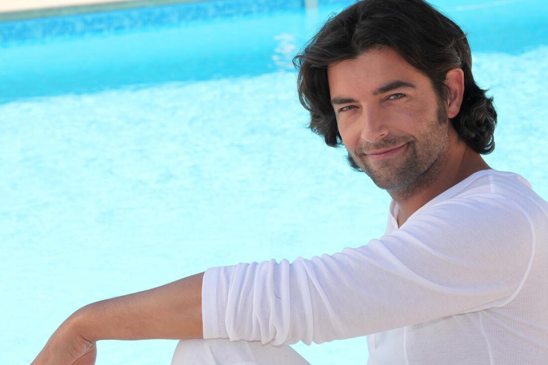 man smiling posing next to pool