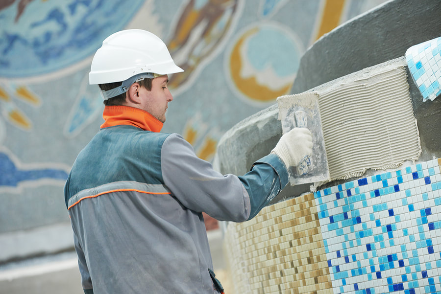 worker is applying tiles to the pool