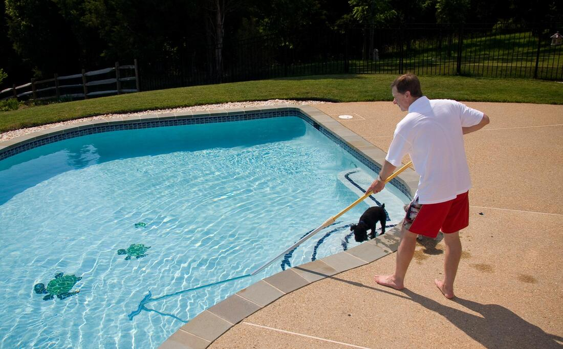 guy is cleaning swimming pool